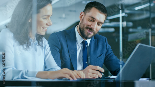 Female Accountant and Male Businessman Sitting at the Desk Having Discussion and Working on a Desktop Computer, Solving Problems. Modern Stylish Office with Beautiful People.