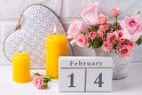 Pink roses flowers, calendar, decorative heart  and  yellow  candles against  white brick wall.