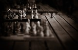 chessboard with figures and one pawn separately in the monochrome abstract photo in style sepia with a vignette and a blank space for the text - 209556497