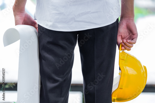 Foto Murales Man holding yellow helmet close up