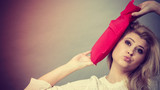 Woman holding red hot water bottle on head - 209562800