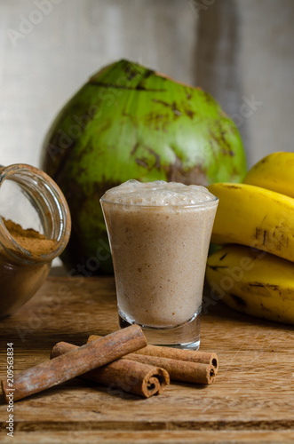 Fotobehang Sap Healthy drink made with coconut, banana, cinnamon and papaya, served in a glass tumbler
