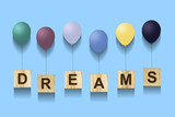 Dreams. An inscription on wooden cubes with multi-colored inflatable balls on a blue background, isolated. The concept of summer holidays. - 209567235