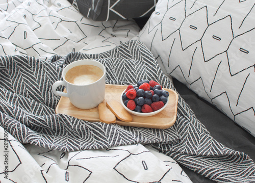 Foto Murales Breakfast bed Wooden tray Hotel room Early morning Concept interior Copy space Geometric sheet and pillow case Berries Cappuccino cup Biscuits Top view