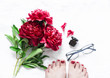 Red flowers peonies, beautiful female feet with red pedicure, glasses, perfume on light background, top view. Beauty concept. Womens still life. Soft focus on the flowers