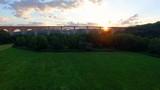 Sun peaking through huge train bridge at sunset for a USA style green land vista! - 209582045