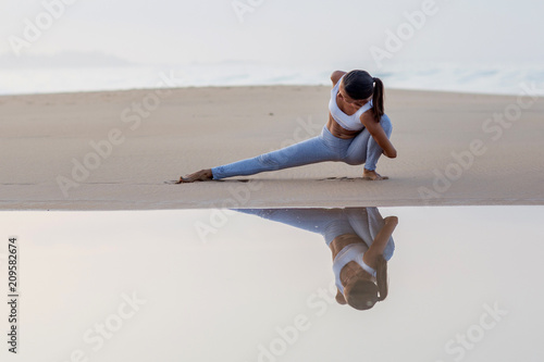Leinwanddruck Bild Caucasian woman practicing yoga at seashore of tropic ocean