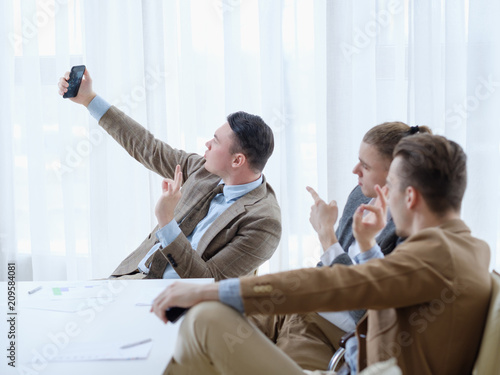 Foto Murales selfie at work. business man have fun at the office meeting taking photos of themselves. successful managers sharing their lifestyle. coaching. ok sign. perfect gesture.