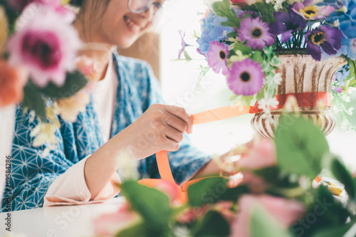 Foto Murales Female hands making beautiful flower composition in floral shop.