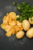 chips recipe. natural food. fried crisps and fresh potatoes with green herbs on dark background - 209585059