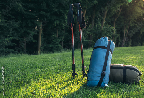 Foto Murales tourist lifestyle , two sleeping bags trekking poles on green grass illuminated by sunlight