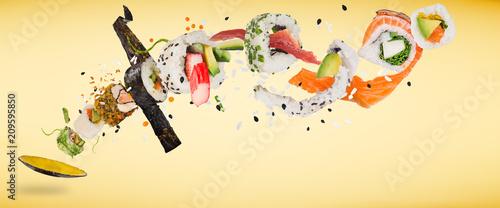 Kawałki pysznego japońskiego sushi zamrożone w powietrzu.