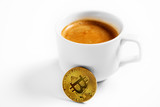 Cryptocurrency golden bitcoin standing on coffee cup