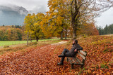 Man sits on a bench and looks at surrounding autumn