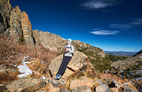 Woman tourist on a trail in Rocky Mountains - 209604834