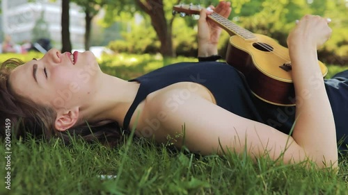 Young woman resting, she play on ukulele, little guitar, lying on grass