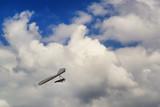 Hang glider pilot soar in thermal updrafts below the clouds. - 209616498