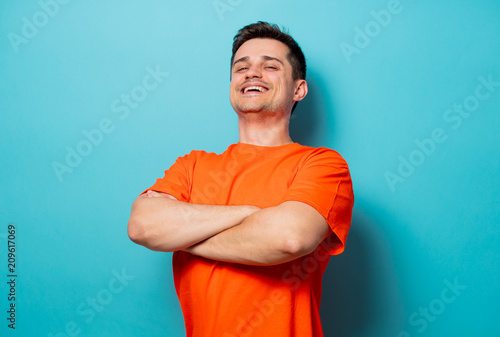 Foto Murales Young handsome man in orange t-shirt. Studio image on blue background