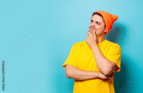 Foto Murales Young handsome man in yellow t-shirt and orange hat on blue background