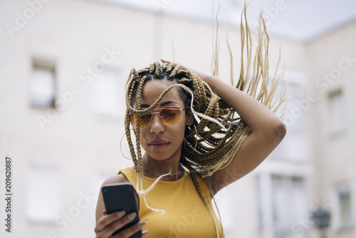 Afro-haired latin woman posing with mobile phone.