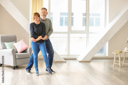 Leinwanddruck Bild Happy mature couple dancing at home