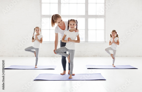 Obraz na płótnie children practicing engaged in gymnastics and yoga with  teacher