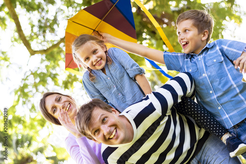 Family playing with a colorful kite - 209629289