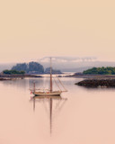 Sailboat moored in a calm flat bay with reflection on the Inside Passage of Alaska with a pink sky and water at dusk. - 209634856