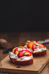Summer fresh fruit toast sandwich with soft white cheese on a vintage rustic table top wood background