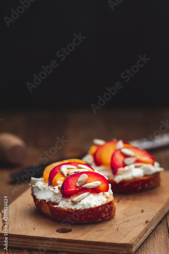 Foto Murales Summer fresh  fruit toast sandwich with soft white cheese on a vintage rustic table top wood background