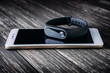 Black fitness tracker on white smartphone on wooden table