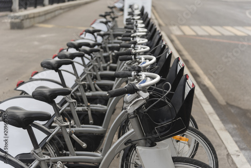 Public bikes in a row in the Parking lot. Bicycle rental in the city