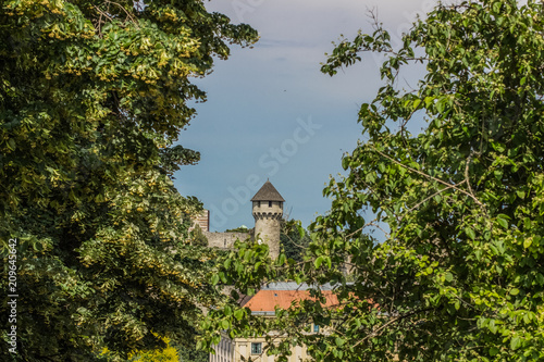 Fridge magnet old small medieval tower between green branches of trees