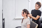 hair stylist making new haircut to brunette woman in salon