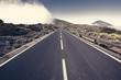 Leinwanddruck Bild - asphalt road running at the foot of the volcano