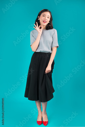 Foto Murales Full body of smiling asian woman dressed in pin-up style dress over blue.