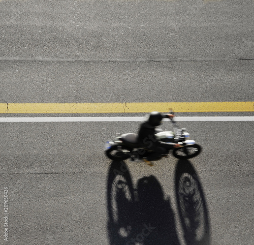 Fast motorbike racing on the road. Taken from above.