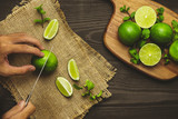 Male hand is slicing lemon on a cutting board - 209651256