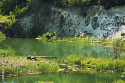Fotobehang Pistache A large military gun made of wood and stone stands on the shores of a beautiful lake in summer time