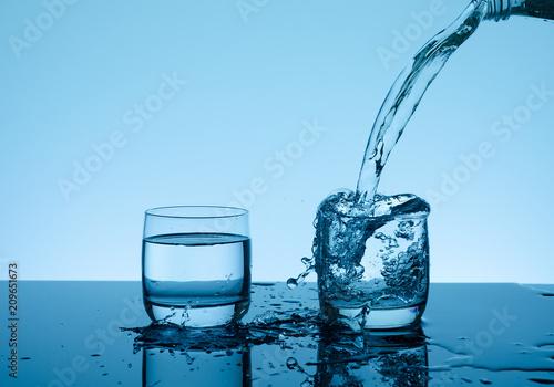 Kreatywnie chełbotanie woda w szkle na błękitnym tle