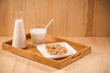 Bottle with milk and glass of milk at wooden table with almond candies. - 209656011