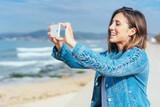 lächelnde junge frau macht ein foto am strand - 209657614