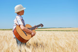 child boy with guitar is in the yellow wheat field, bright sun, summer landscape - 209657630