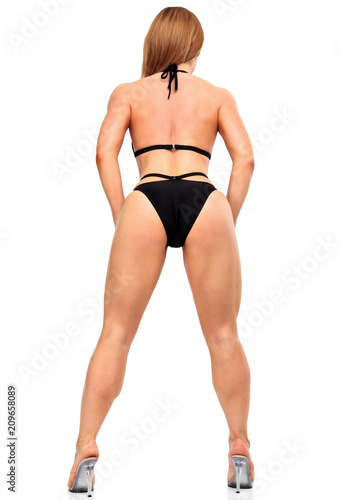 Sexy woman in black bikini is posing against a white background, isolated