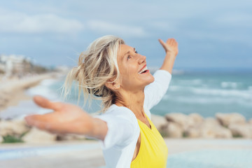 ältere Frau steht mit ausgebreiteten armen am strand und genießt den Urlaub