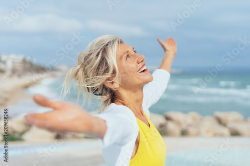 Foto Murales ältere Frau steht mit ausgebreiteten armen am strand und genießt den Urlaub