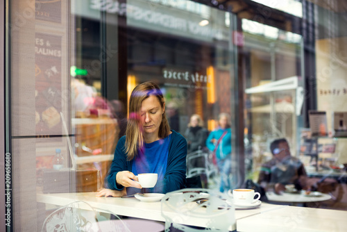Foto Murales beautiful woman drinking coffee in the cafe