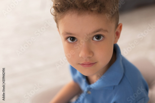 Handsome boy. Handsome dark-eyed little boy with nice dark curly hair feeling very satisfied while playing at home