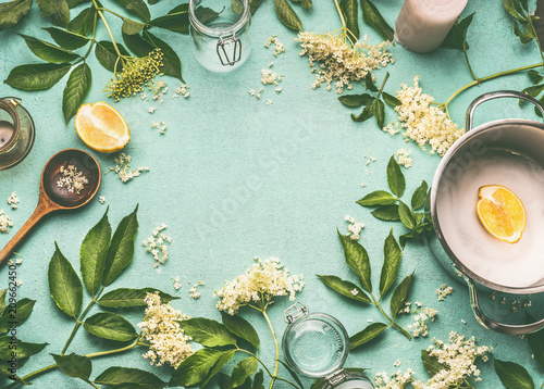 Elder flowers cooking preparation. Frame of Elder flowers with spoon, pot, sugar and lemon on blue table background, top view