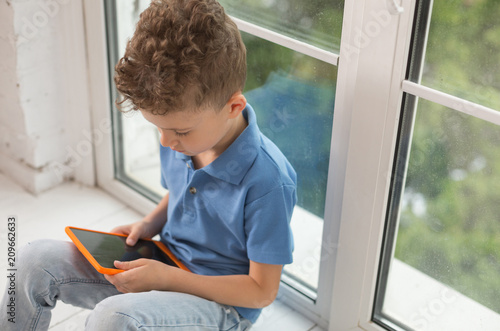 Laptop games. Handsome curly boy in stylish polo shirt playing funny games on laptop while sitting near window in the kitchen